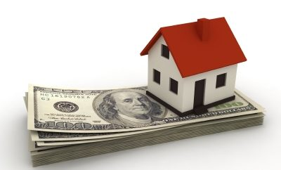 house on a stack of hundred dollar bills rpresenting paying a mortgage