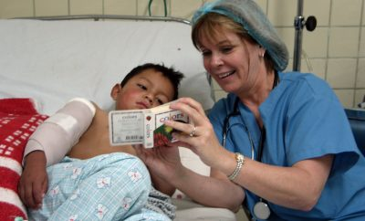 nurse and child in hospital bed