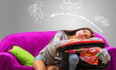 girl daydreaming of travel on pink couch
