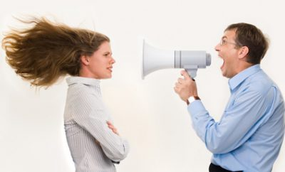 man speaking to woman through megaphone