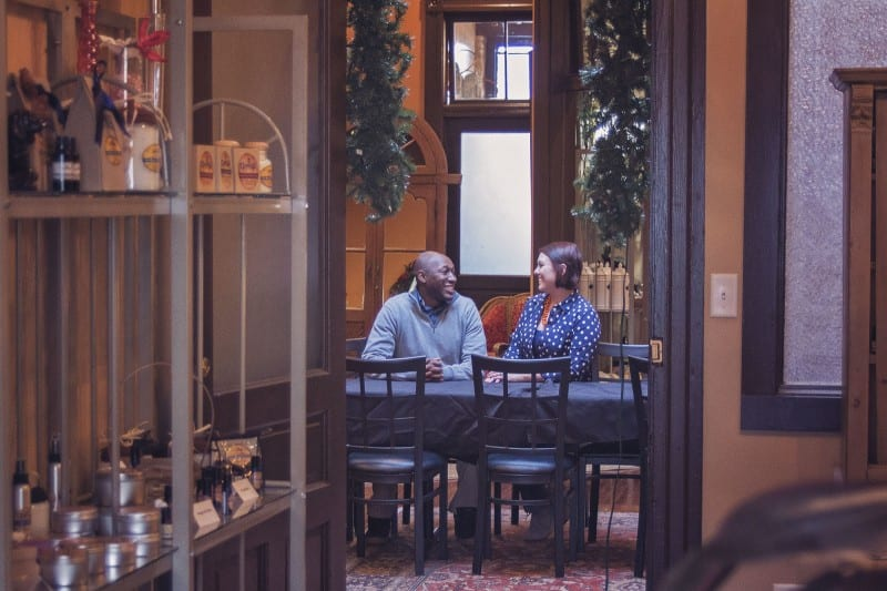 couple sitting at table laughing talking about why to live with your partner