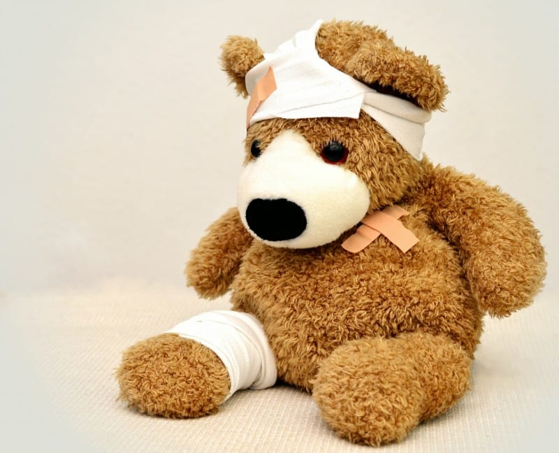 teddy bear wearing bandages from his trip to go to the doctor