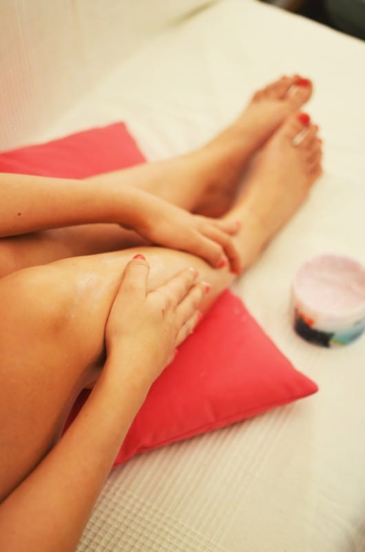 woman exfoliating her legs to maintain a beauty regime