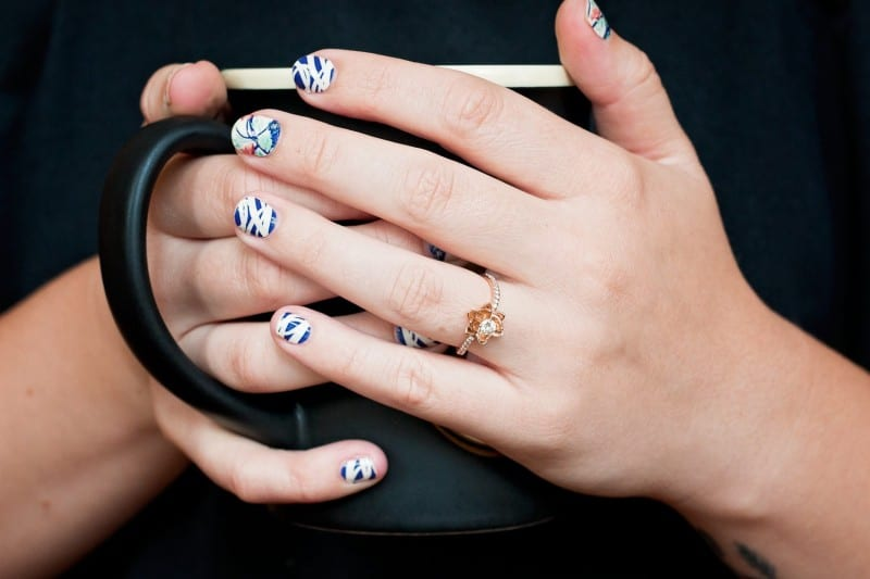 hands holding coffee cup wearing nail strips that make great stocking stuffers