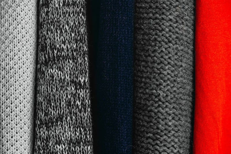 close-up of multi-colored sweaters for a capsule wardrobe