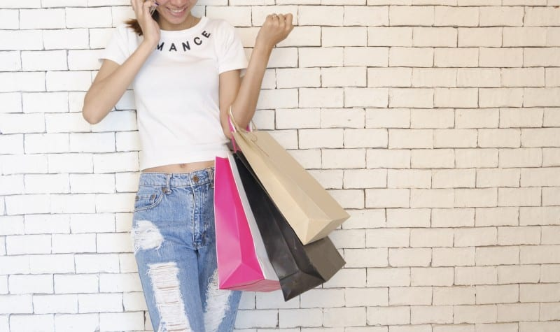 woman on the phone holding shopping bags full of over the shoulder boulder holders