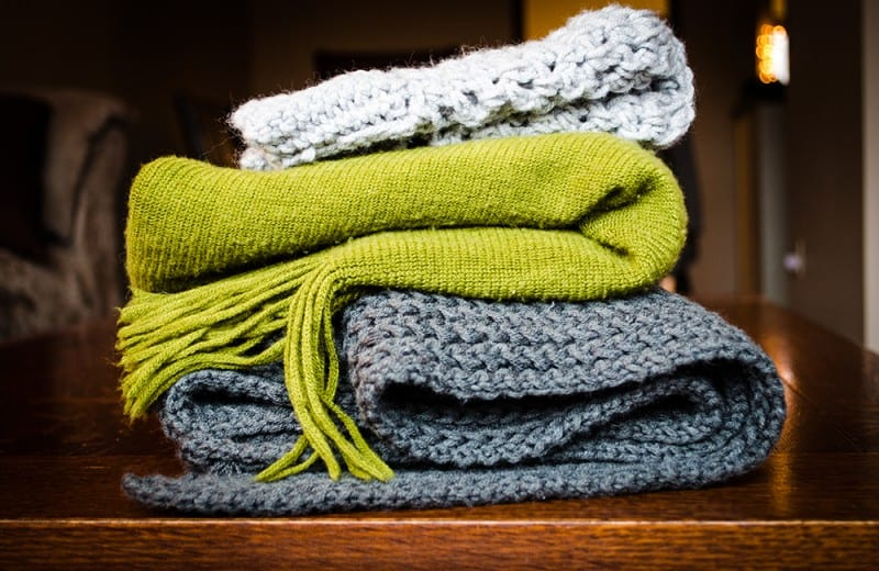 sweaters stacked up for a capsule wardrobe